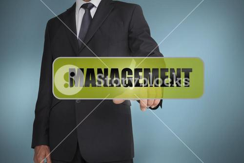 Businessman touching the word management written on green tag