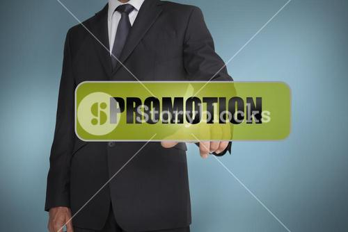 Businessman touching the word promotion written on green tag