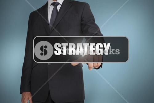 Businessman touching the word strategy written on black tag