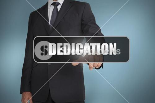 Businessman touching the word dedication written on black tag