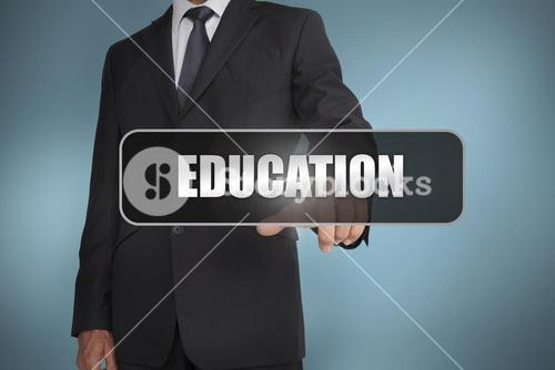 Businessman touching the word education written on black tag