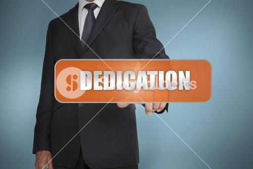 Businessman selecting the word dedication written on orange tag