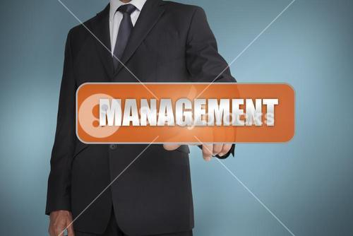 Businessman selecting the word management written on orange tag