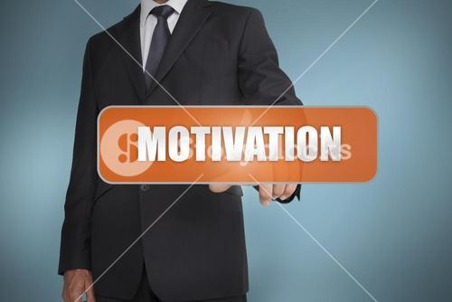 Businessman selecting the word motivation written on orange tag