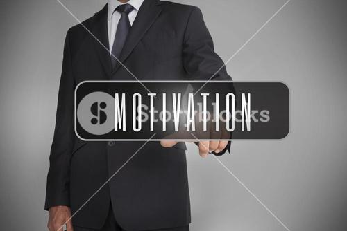 Businessman selecting the word motivation written on black tag