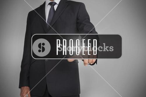 Businessman selecting label with proceed written on it