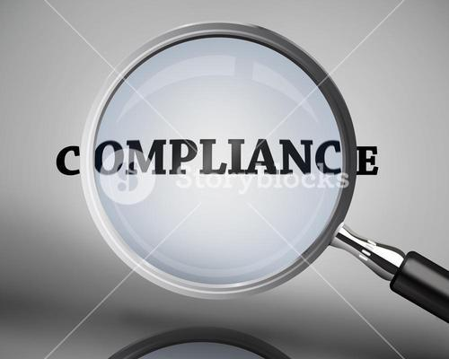 Magnifying glass showing compliance word