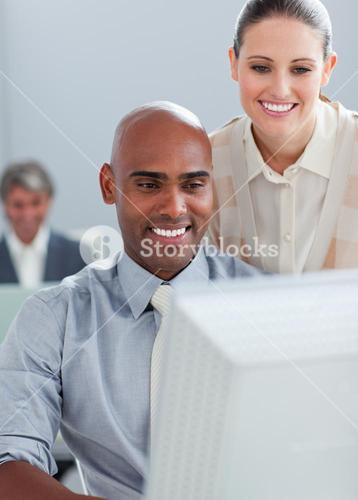 Confident businesswoman helping her colleague at a computer