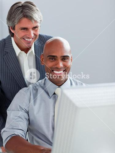 Mature businessman helping his colleague at a computer