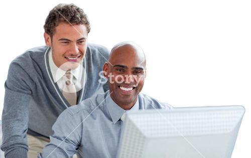 Two young businessmen working at a computer in the office