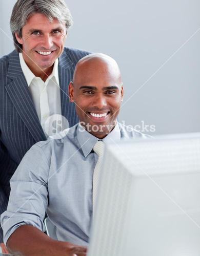 Two elegant businessmen working at a computer