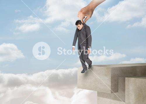 Giant hand dropping off a businessman over the clouds