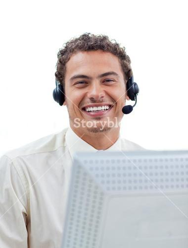 Positive businessman talking on headset at a computer