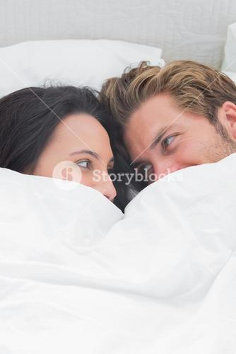 Couple under the quilt looking at each other
