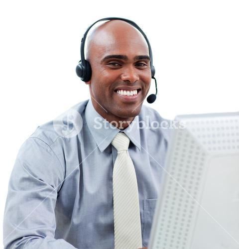 Happy businessman talking on headset at a computer