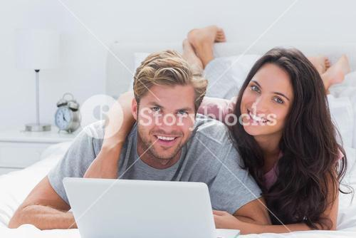 Happy couple with a laptop in bed