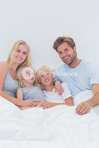 Portrait of a happy family in bed