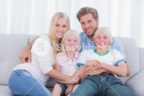 Smiling family sitting on couch