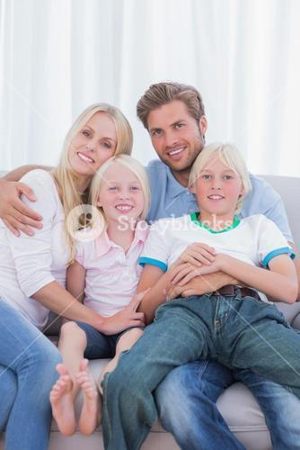 Parents and children sitting together on couch