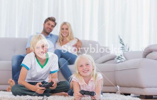 Children sitting on the carpet playing video games