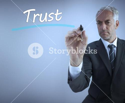 Businessman writing the word trust