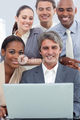 Business group showing diversity working at a laptop