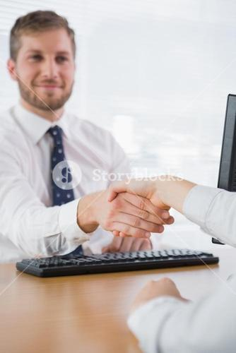 Smiling businessman shaking hands withco worker