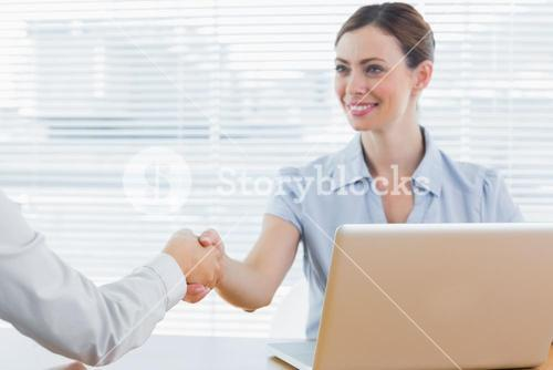 Businesswoman shaking hands with colleague