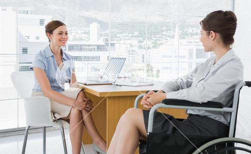 Businesswoman chatting with disabled colleague