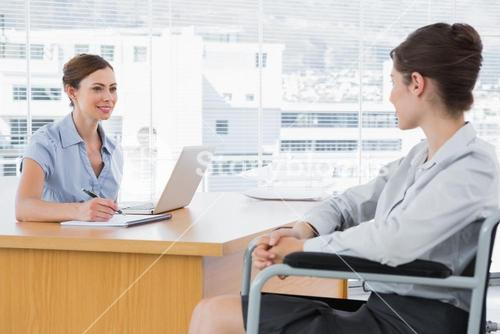 Businesswoman interviewing disabled candidate