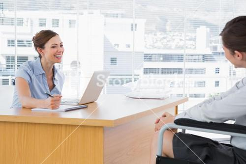 Businesswoman smiling at disabled job candidate