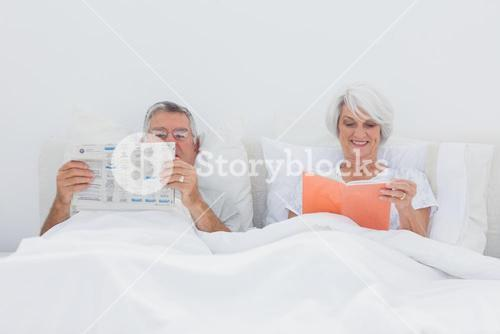 Mature people reading in bed