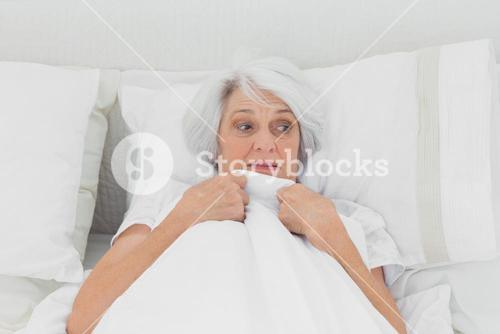 Fearful woman clutching her quilt