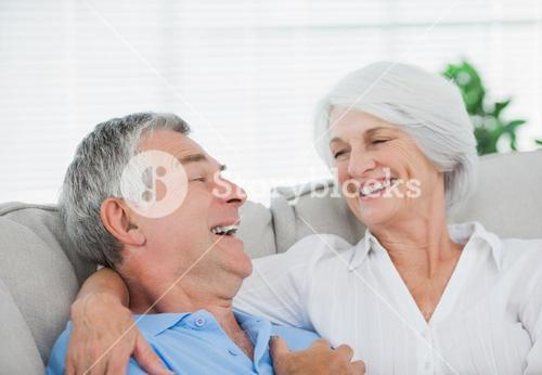 Couple laughing and chatting on couch