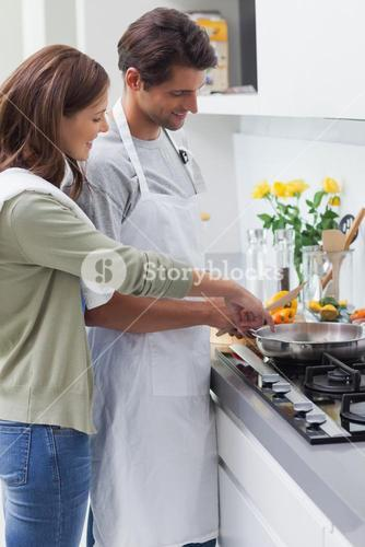 Delighted couple cooking