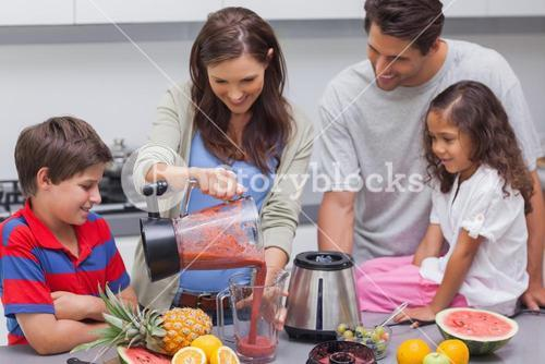 Woman with family pouring fruit from a blender