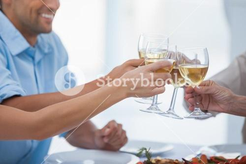 Close up of hands clinking glasses of white wine