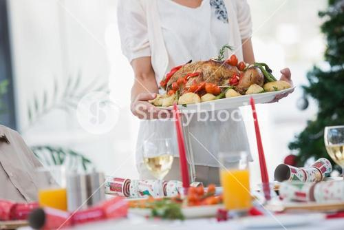 Woman bringing roast chicken at table