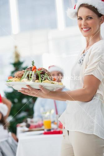 Attractive woman bringing roast chicken at a christmas dinner