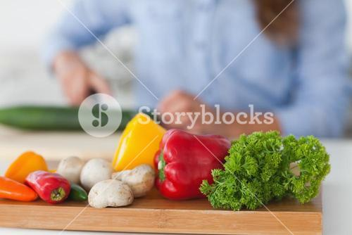 Wooden board with vegetables on a table