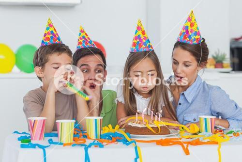 Little girl blowing her candles during her birthday party
