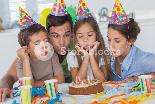 Family blowing candles together