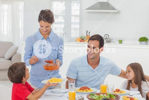 Woman giving pasta sauce to her son