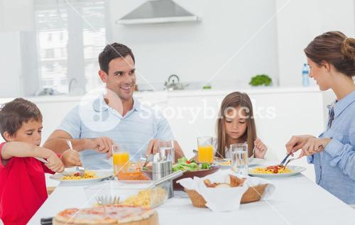 Family eating pasta with sauce