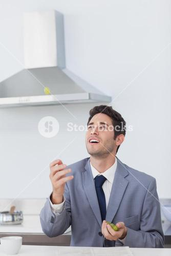 Businessman throwing grape in the air