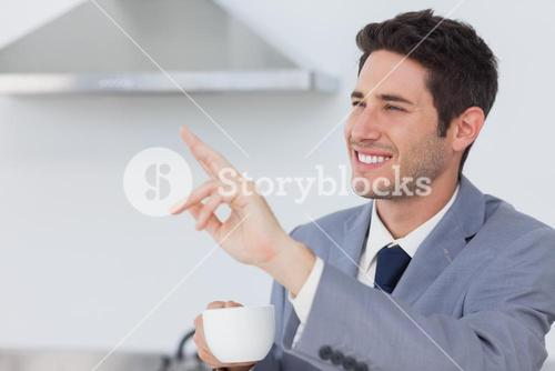 Businessman waving at someone in the kitchen