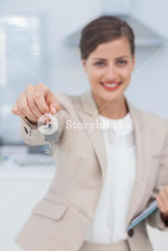 Pretty real estate agent offering house key
