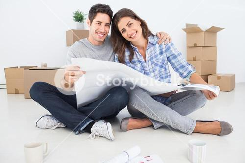 man and woman holding house plans