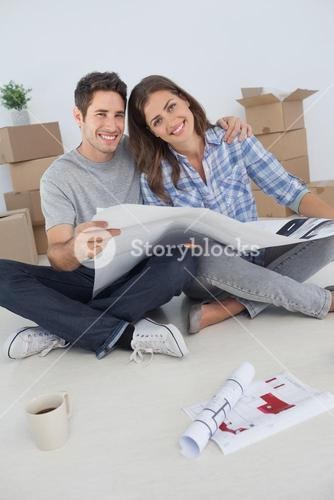 Portrait of man and his wife holding house plans