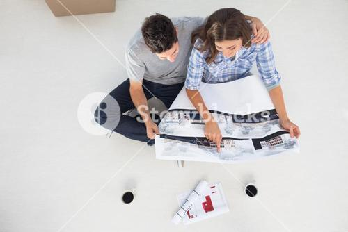 Overview of a husband and his wife looking at house plans